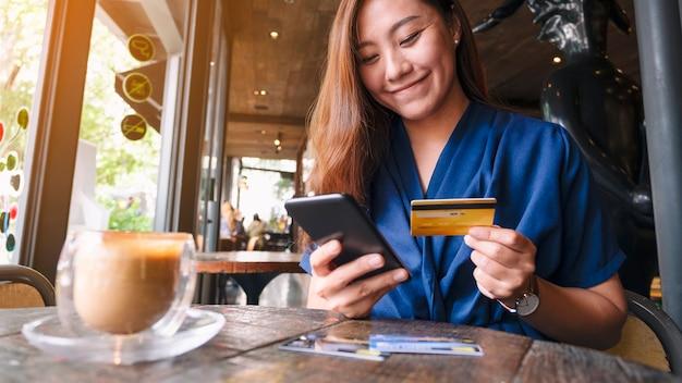 Zbliżenie obraz azjatyckiej kobiety za pomocą karty kredytowej do zakupów i zakupów online na telefonie komórkowym