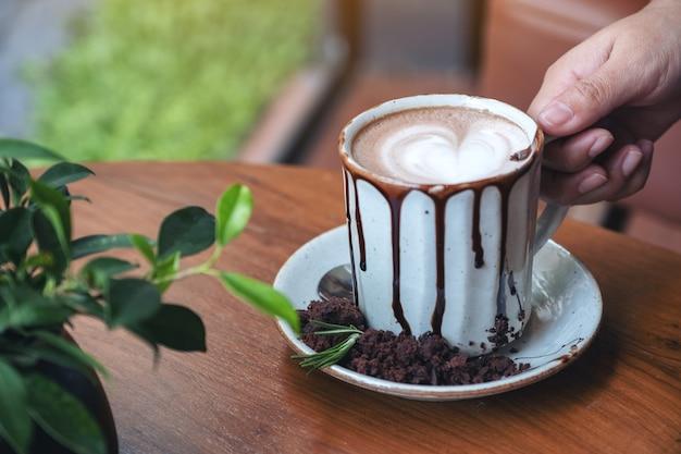 Zbliżenie obraz dłoni trzymającej kubek gorącej czekolady na drewnianym stole w kawiarni