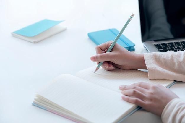Zbliżenie obraz kobiecej dłoni pisania na notebooku z ołówkiem.