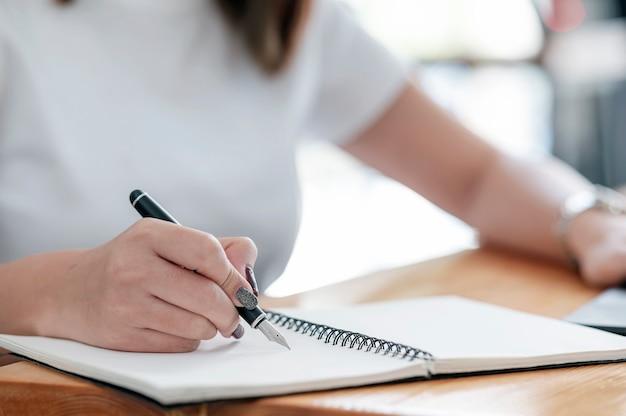 Zbliżenie obraz kobiecej dłoni pisania na notebooku za pomocą pióra, siedząc przy stole.