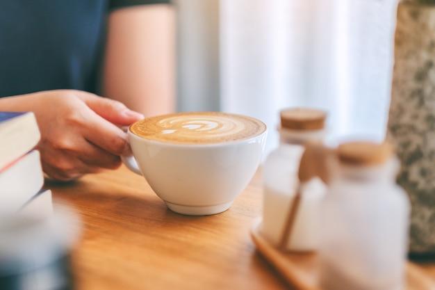 Zbliżenie obraz kobiecej ręki trzymającej białą filiżankę gorącej kawy z książkami na drewnianym stole