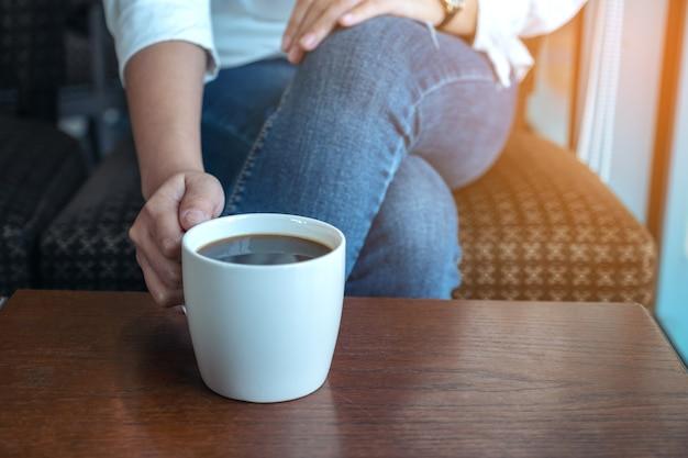 Zbliżenie obraz kobiecej ręki trzymającej filiżankę gorącej kawy do picia siedząc w kawiarni