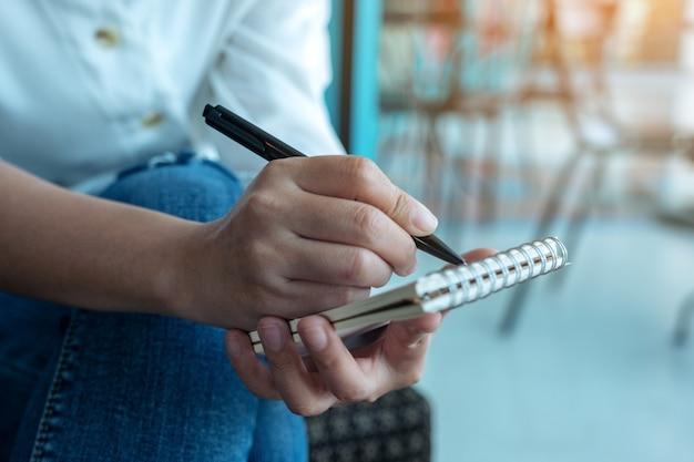 Zbliżenie obraz kobiety trzymając się za ręce i pisania na pustym notatniku