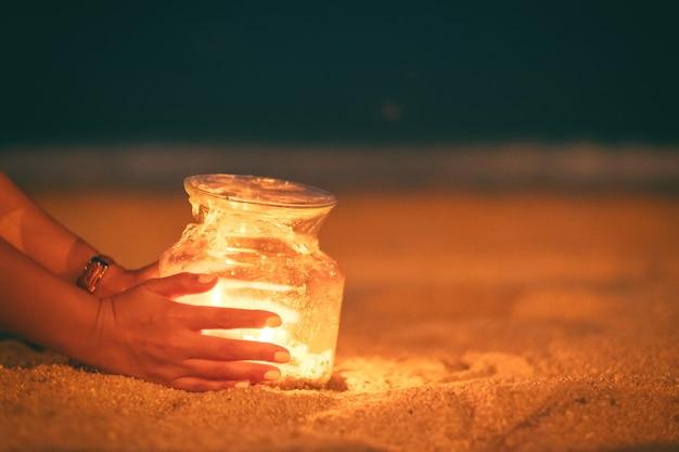 Zbliżenie obraz kobiety trzymając się za ręce i stawiając posiadacze szklanych butelek świece na plaży w nocy