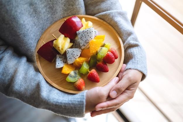 Zbliżenie obraz kobiety trzymającej drewniany talerz świeżych owoców mieszanych na szaszłykach