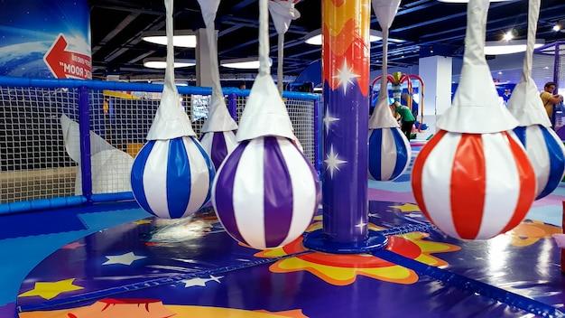 Zbliżenie obraz kolorowej dziecięcej karuzeli i huśtawki na placu zabaw pokrytym miękkimi matami dla bezpieczeństwa dzieci