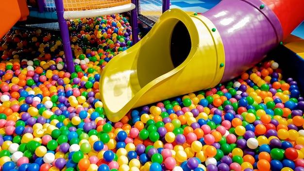 Zbliżenie Obraz Kolorowy Slajd Na Plac Zabaw Dla Dzieci Z Dużą Ilością Małych Plastikowych Piłek W Basenie. Premium Zdjęcia