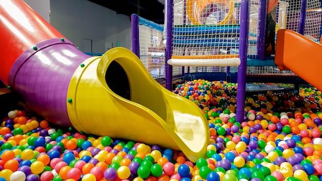 Zbliżenie obraz kolorowy slajd na plac zabaw dla dzieci z dużą ilością małych plastikowych piłek w basenie.