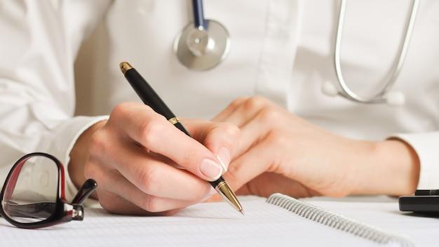Zbliżenie obraz lekarza zapisując na białym pustym notatniku na drewnianym stole. białe tło, selektywna ostrość. pojęcie medyczne i biznesowe.