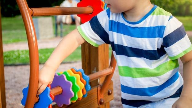 Zbliżenie obraz małego chłopca bawiącego się na placu zabaw i obracających się drewnianych pierścieni