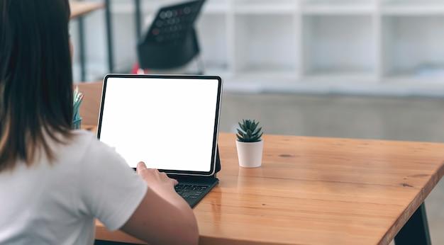 Zbliżenie obraz młodej kobiety pracy na komputerze typu tablet, siedząc przy stole w co-roboczym.