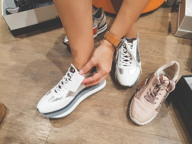 Zbliżenie obraz młodej kobiety siedzącej w centrum handlowym i przymierzającego nowe buty