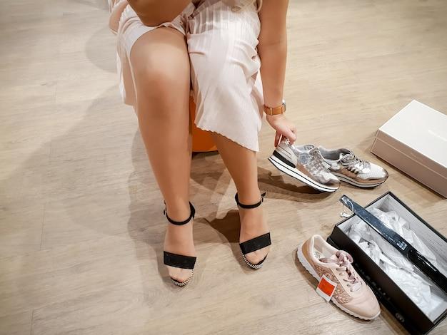 Zbliżenie obraz młodej kobiety w spódnicy, siedząc w szatni i przymierzając nowe buty w sklepie