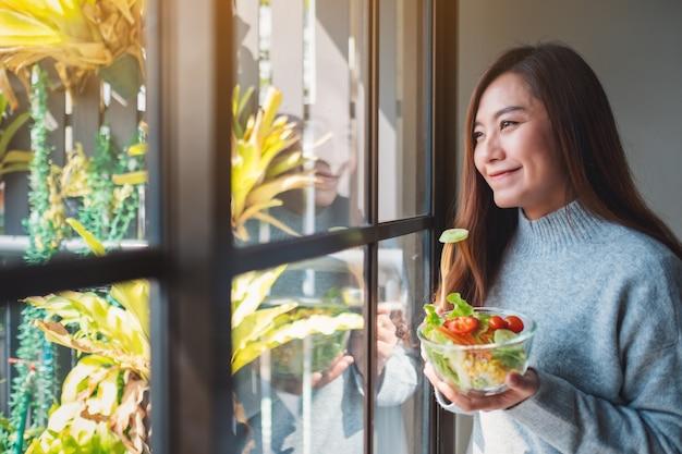 Zbliżenie obraz pięknej azjatyckiej kobiety jedzącej i trzymającej miskę sałatki ze świeżych warzyw mieszanych