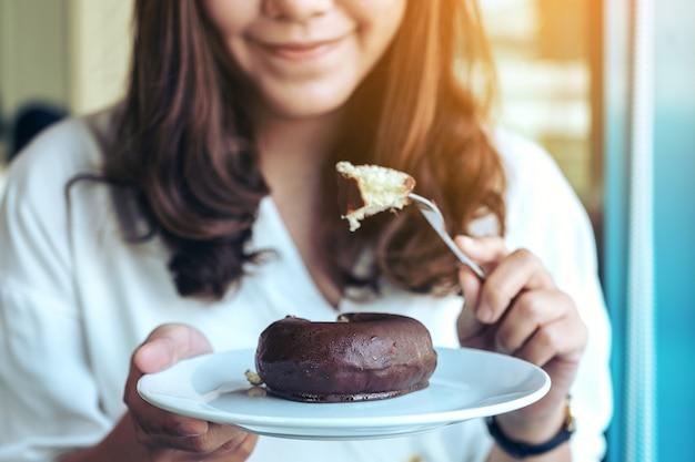 Zbliżenie obraz pięknej kobiety, trzymając widelec i jeść pączek czekolady na białym talerzu