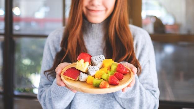 Zbliżenie obraz pięknej kobiety trzymającej drewniany talerz świeżych mieszanych owoców na szaszłykach