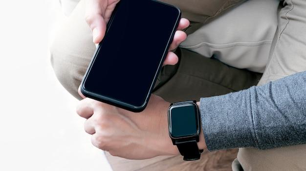Zbliżenie obraz ręki człowieka noszenia smartwatcha i trzymając smartfon pusty ekran.