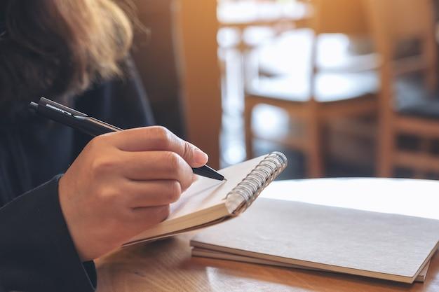 Zbliżenie obraz ręki trzymającej i pisania na pustym notatniku na stole w kawiarni