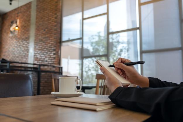 Zbliżenie obraz ręki trzymającej i pisania na pustym notatniku z filiżanką kawy na stole w kawiarni