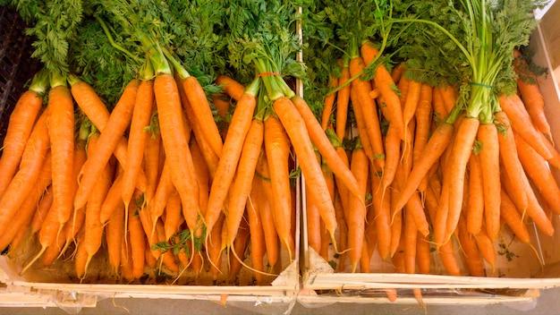 Zbliżenie obraz świeżych dojrzałych marchwi leżącego w drewnianej skrzyni na ladzie w sklepie. zbliżenie tekstury lub wzór świeżych dojrzałych warzyw. piękne tło żywności