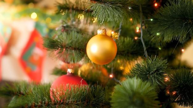 Zbliżenie obraz złotej bombki świątecznej wiszącej na jodły w salonie domu przed kominkiem