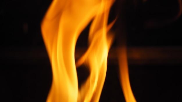 Zbliżenie obrazów ognia lub płomienia płonącego na czarnym tle, które reprezentują moc gorąca