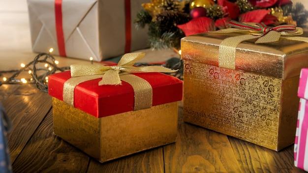 Zbliżenie obrazu czerwonych i złotych pudełek na prezenty świąteczne na drewnianej podłodze