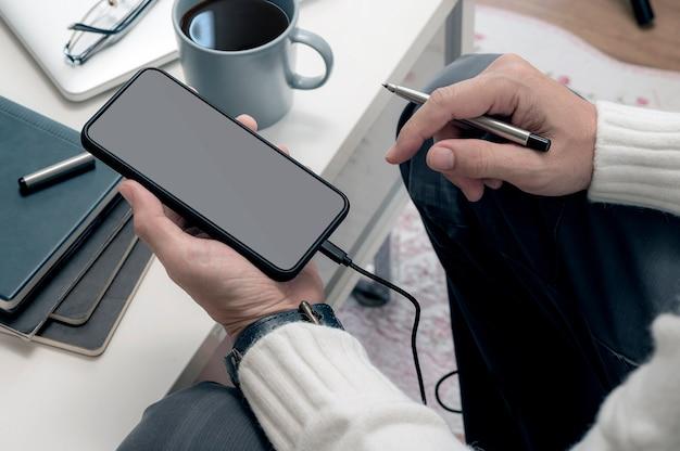 Zbliżenie obrazu człowieka ręki trzymającej pusty ekran smartfona siedząc w salonie