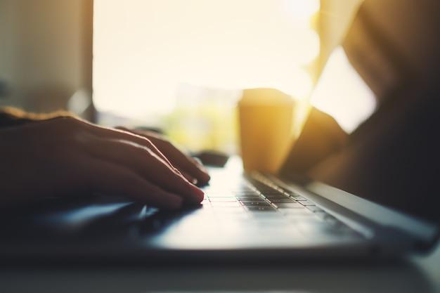 Zbliżenie obrazu dłoni kobiety, która pracuje i pisze na komputerze przenośnym na stole