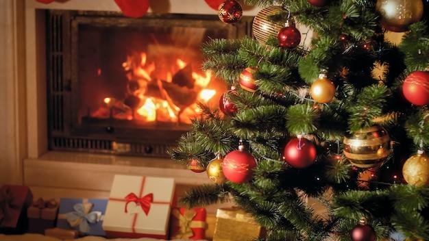 Zbliżenie obrazu dużego stosu prezentów świątecznych i prezentów obok płonącego kominka i ozdobionej choinki