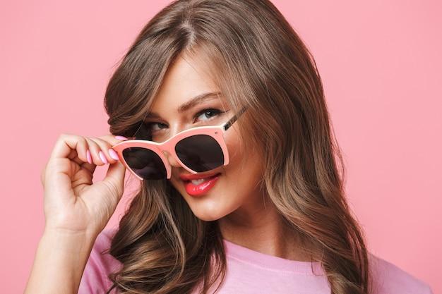 Zbliżenie obrazu europejskiej kobiety dwudziestki z długą kręconą fryzurą patrząc na kamerę z pięknym uśmiechem spod modnych okularów przeciwsłonecznych, odizolowane na różowym tle