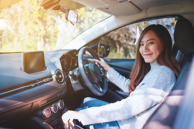 Zbliżenie obrazu kobiety kierowcy zmieniającej automatyczną dźwignię zmiany biegów podczas jazdy samochodem