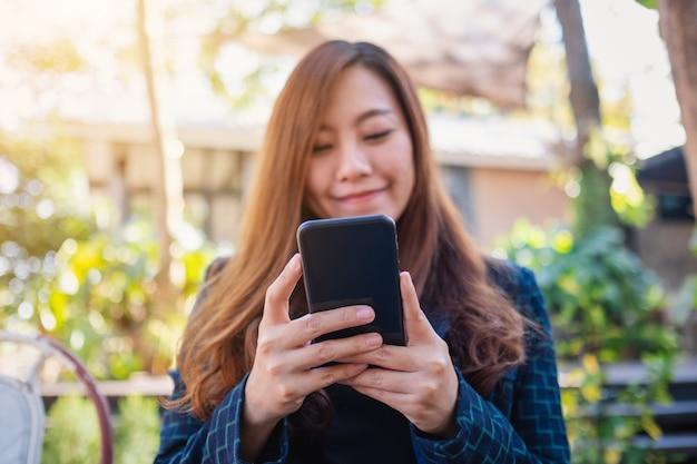 Zbliżenie obrazu kobiety trzymającej, używającej i patrzącej na telefon komórkowy w plenerze