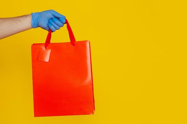 Zbliżenie obrazu koncepcji dostawy. ręka w niebieskich rękawiczkach trzymająca duży kolorowy worek nad żółtym