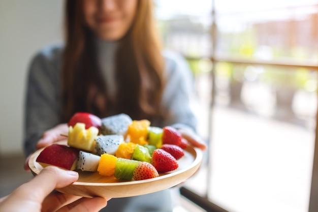 Zbliżenie obrazu ludzi podających kobiecie drewniany talerz świeżych mieszanych owoców na szaszłykach