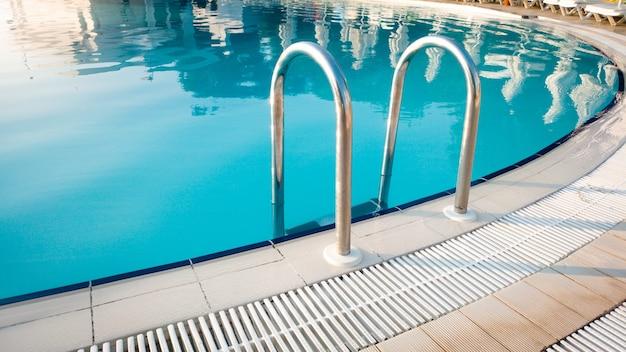 Zbliżenie obrazu metalowych poręczy na schodach przy odkrytym basenie