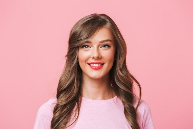 Zbliżenie obrazu młodej europejskiej kobiety w wieku 20 lat z długimi kręconymi fryzurami i wieczorowym makijażem uśmiecha się do kamery ze szczęśliwym spojrzeniem, odizolowane na różowym tle
