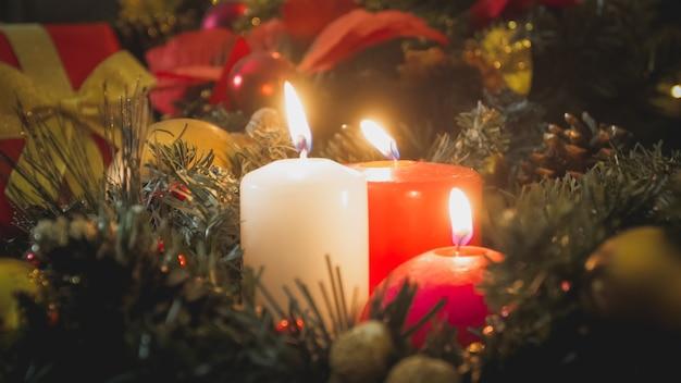 Zbliżenie obrazu płonących świec i wieniec adwentowy w salonie