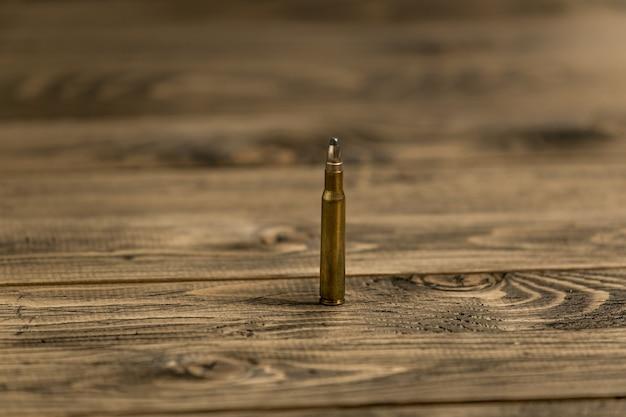 Zbliżenie obrazu pocisku karabinowego kałaszikowa na starym drewnianym biurku