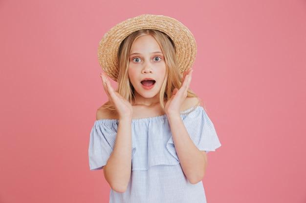 Zbliżenie obrazu podekscytowanej dziewczyny europejskiej 8-10 ubrana w niebieską letnią sukienkę i słomkowy kapelusz podnosząc ręce na twarz ze zdziwienia, odizolowane na różowym tle