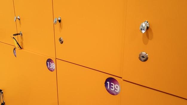 Zbliżenie obrazu prostych, długich rzędów żółtych szafek w szkole lub na studiach