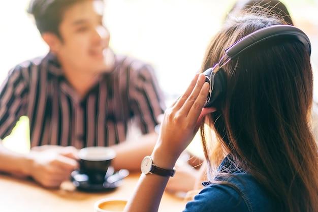 Zbliżenie obrazu przyjaciół lubiło rozmawiać, słuchać muzyki przez słuchawki i pić kawę razem w kawiarni