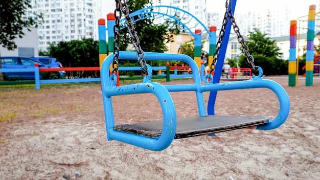 Zbliżenie obrazu pustych metalowych huśtawek na placu zabaw dla dzieci