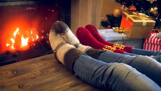 Zbliżenie obrazu rodzinnych stóp w wełnianych skarpetkach leżących na drewnianym stole obok płonącego kominka