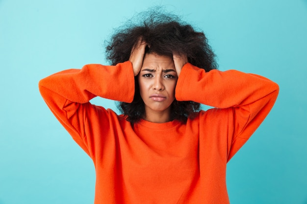 Zbliżenie obrazu sfrustrowanej kobiety w czerwonej koszuli, patrząc i chwytając głowę z kudłatymi włosami, odizolowane na niebieskiej ścianie