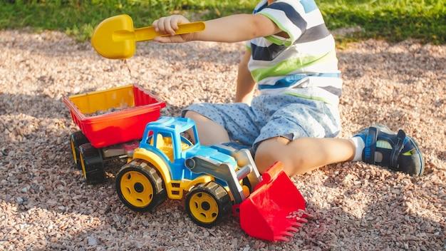 Zbliżenie obrazu ślicznego małego chłopca bawiącego się na placu zabaw z zabawkami
