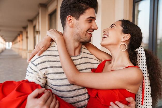 Zbliżenie obrazu szczęśliwego romantycznego mężczyzny niosącego kobietę w rękach i śmiejącego się podczas spaceru w pobliżu pięknego budynku