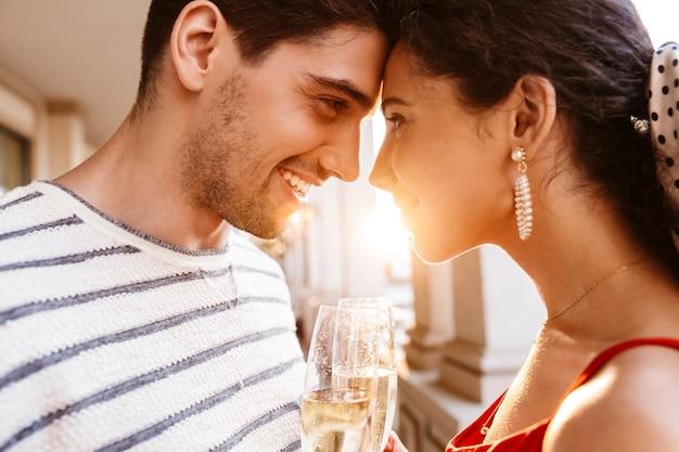 Zbliżenie obrazu szczęśliwej młodej pary patrzącej na siebie i pijącej szampana w pobliżu kolumnad
