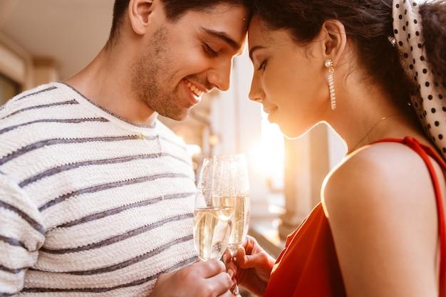 Zbliżenie obrazu szczęśliwej młodej pary stojącej głowa w głowę i pijącej szampana w pobliżu kolumnad