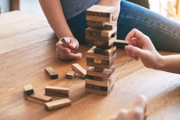Zbliżenie obrazu trzech przyjaciół siedzących i grających razem w grę z drewnianymi klockami tumble tower